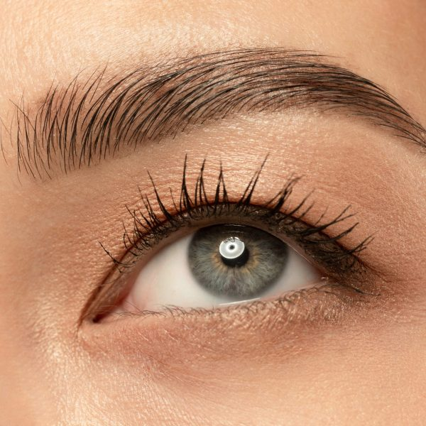 Beautiful young woman's eye close-up shot. Female model with well-kept skin. Perfect skincare, human emotions, facial expression, beauty and cosmetics concept. Deep blue-gray color and eyebrows.